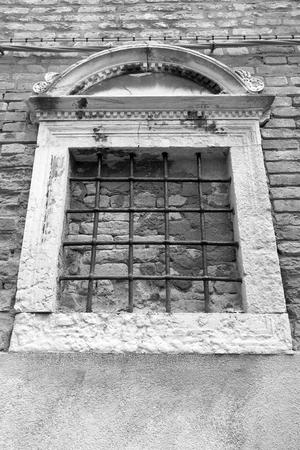 lattice window: old brick facade of the ancient building with a window and a lattice in retro style Stock Photo