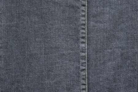 threadbare: denim or rough cotton fabric or jeans material with the stitched seam for the textile textured background of pale color