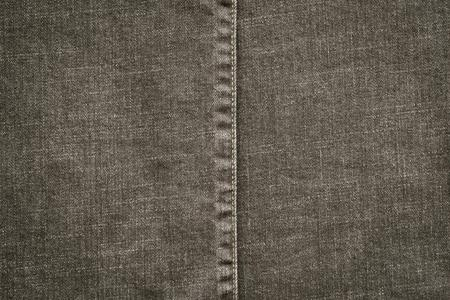 threadbare: denim or rough cotton fabric or jeans material with the stitched seam for the textile textured background of gray color Stock Photo