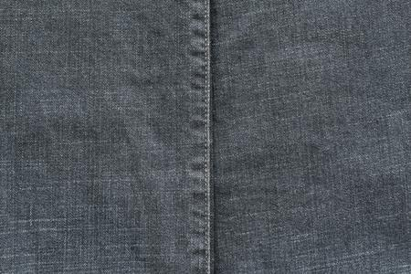 threadbare: denim or rough cotton fabric or jeans material with the stitched seam for the textile textured background