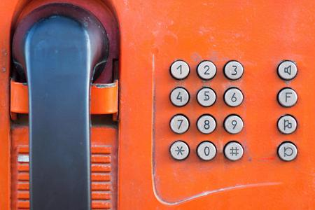 payphone: fragment or part of the old payphone of red color and with a push button set of number closeup Stock Photo