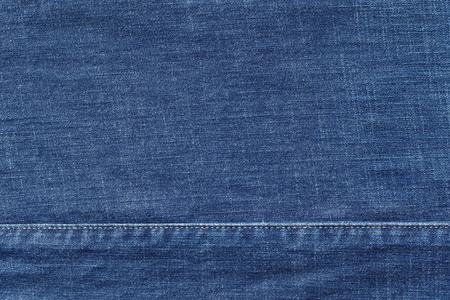 threadbare: denim or rough cotton fabric or jeans material with the stitched seam for the textile textured background of blue color