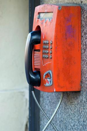 payphone: the big old payphone of red color a closeup and located outdoor on a wall