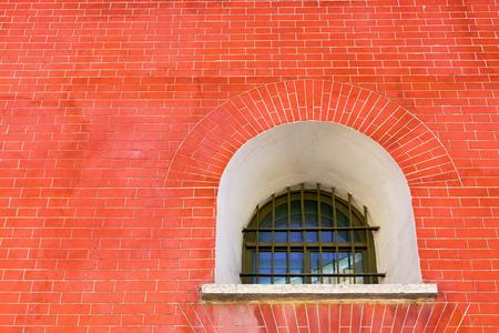 ancient prison: fragment of a brick wall of ancient fortress or prison with one window for a vintage architectural background of red color