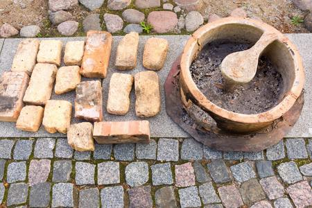 abstractly: the small ancient stone or clay stove for cooking is abstractly located on the stone sidewalk near old bricks Stock Photo