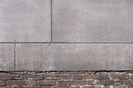 grained: old texture of the destroyed brick wall with grained cement plaster for architectural background and for vintage wallpaper