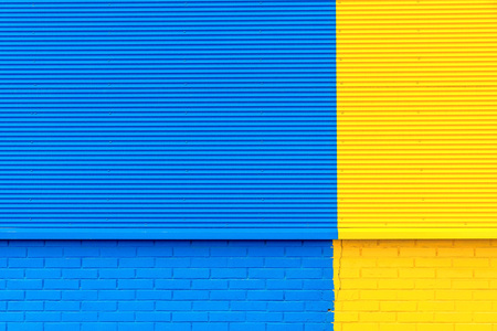 the textured background from corrugated iron and a brick of yellow and blue color and a blank space for the text
