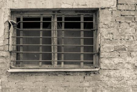 lattice window: old window closeup with a rusty lattice on an ancient brick wall of beige tone and a blank space