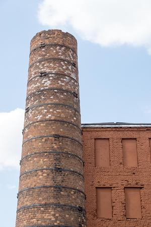 niches: big old chimney closeup against the sky and part of a brick wall with niches for windows