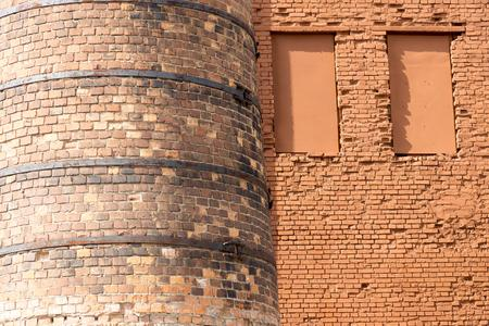 niches: big old chimney closeup and part of a brick wall with niches for windows and blank space Stock Photo