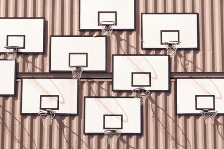 ring tones: the abstract composition of group of basketball baskets of monochrome tone of brown color with rectangular boards is located on a wall of iron containers Stock Photo