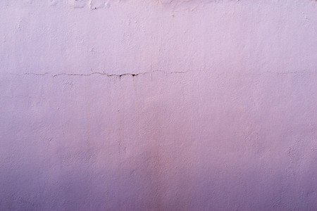 tonality: the abstract textured background of an old surface of the plastered wall of a motley lilac color tonality