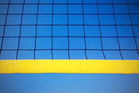black grid with the yellow edging for playing volleyball closeup against the background of the blue sky