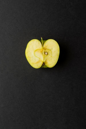longitudinal cut or section of one apple as the isolated object closeup on black or against a dark background Stock Photo