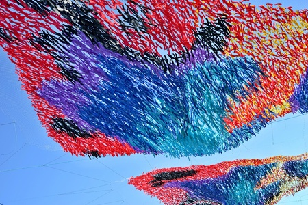 festive abstract tinsel closeup from color tapes of fabric or from textile material against the background of the blue sky