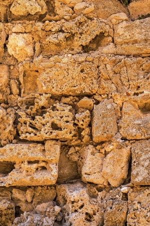 rough porous texture of stone bricks of an old and ancient wall
