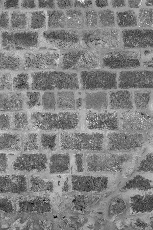 rough porous texture of stone bricks of an old and ancient wall of monochrome tone Stock Photo
