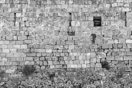 old stone wall of ancient fortress for a background with vintage texture of monochrome tone