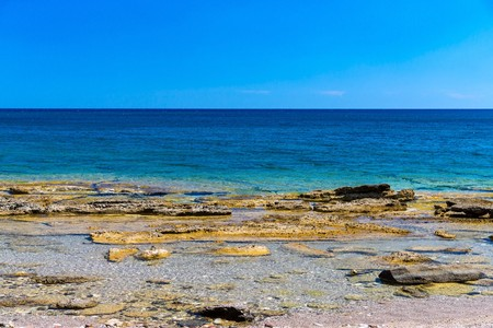 wild sea landscape with the stony coast and with the horizon over water Stock Photo