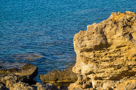 ripple: isolated big stones of the coast on an indistinct background of the blue sea