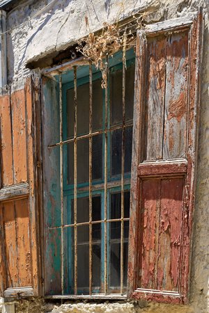 very old window with an iron lattice and with a wooden sun blind Stock Photo