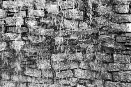 background texture: wet stone brick wall with water splashes for the abstract textured background of monochrome tone Stock Photo