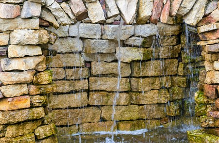 background texture: background and texture a stone wall with an arch and water streams with splashes Stock Photo