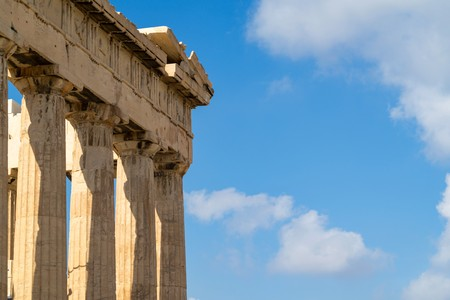 fragment of Ancient Greek architectural elements closeup against the background of the blue sky with white clouds