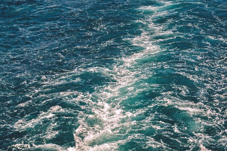 background and abstract texture of a turbulence of the made foam sea water behind a vessel stern