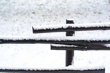 part of an old wooden fence closeup in the winter on an indistinct background of white snow