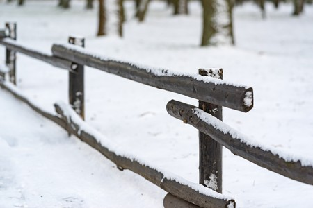 old wooden fence closeup in the winter on an indistinct background of white snow