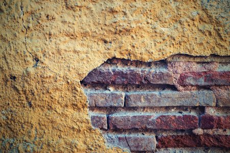 the combined texture of the old peeled plaster on a surface of a brick wall closeup