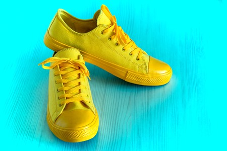 fashionable and beautiful sports activities footwear or for comfortably to go yellow color closeup on a blue background Stok Fotoğraf