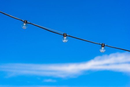 three electric bulbs on one wire against the background of the blue sky with a white cloud