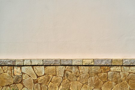 the empty plastered wall with the stone textured plinth for a background or for wallpaper Banque d'images - 116866428