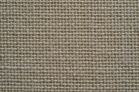 texture of rough fabric or textile material with a perepoleteniye closeup for a fashionable background or for wallpaper of beige color