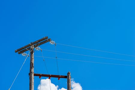 old wooden columns for the power line on an empty background of the blue sky Stock Photo