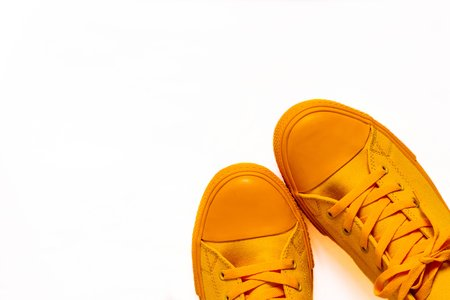 fashionable sports shoes or gym shoes a closeup of orange color separately on a white background