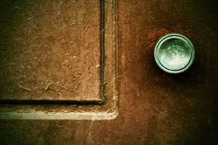 part of an old wooden door with the round metal handle and a blank space closeup in the photo in retro style