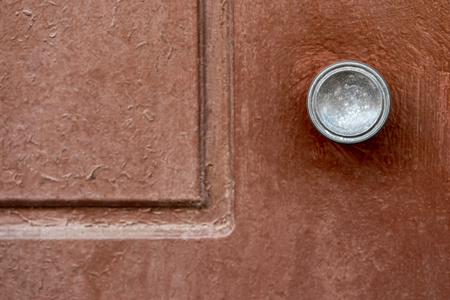 part of an old wooden door with the round metal handle and a blank space closeup Banco de Imagens