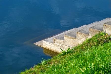 small concrete step descent to a reservoir closeup and a hillock with a green grass Banco de Imagens