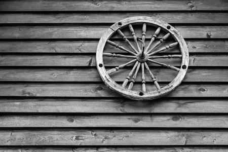 one big old wooden spoke wheel for the ancient mechanism or for the ancient equipment and closeup on a wall from wooden boards and in the foreground of monochrome tone. Stok Fotoğraf