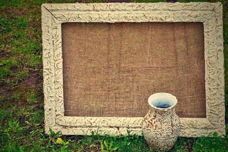 one retro a frame for a picture with a blank space for the text and one vintage jug closeup on a lawn in the photo in a retro style. Stok Fotoğraf