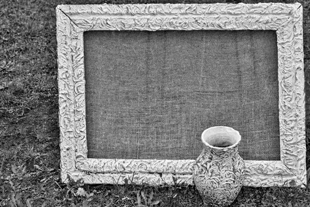 one retro a frame for a picture with a blank space for the text and one vintage jug closeup on a lawn in the photo of monochrome tone.