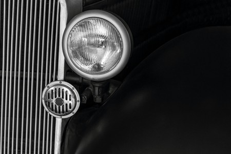 front part of retro of the car closeup with headlight and with sound signal on radiator lattice of monochrome tone Stok Fotoğraf