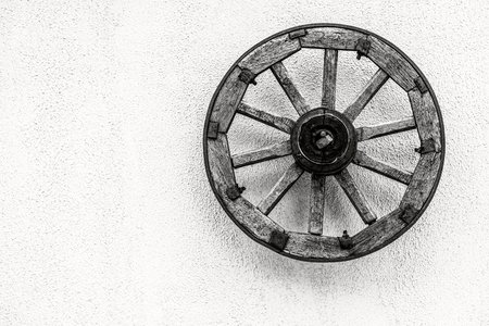 one big old wheel of the ancient animal-drawn vehicle or the cart and closeup against the background of the empty plastered wall of monochrome tone. Stok Fotoğraf