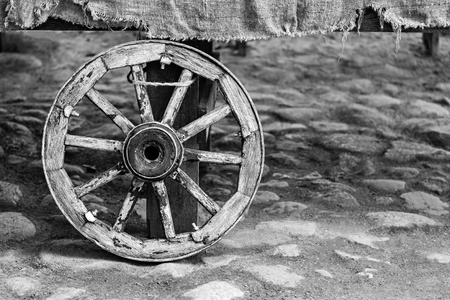 one big old wheel for the ancient animal-drawn vehicle or for the cart and closeup in the foreground of monochrome tone