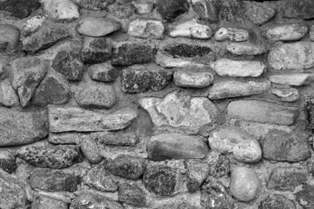 the abstract textured background of an old stone wall in vintage style of monochrome tone and closeup