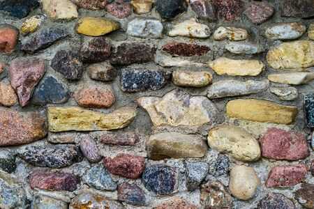 the abstract textured background of an old stone wall in vintage style and closeup Reklamní fotografie