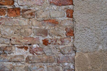 die alte verputzte Backsteinmauer mit der zerstörten Oberfläche für einen Vintage-Hintergrund Standard-Bild